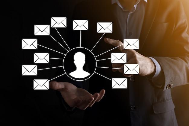 Mano masculina que sostiene el icono de la letra, los iconos de correo electrónico. póngase en contacto con nosotros por correo electrónico del boletín y proteja su información personal del correo no deseado. centro de llamadas de servicio al cliente contáctenos.