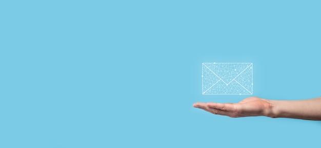 Mano masculina que sostiene el icono de la letra, los iconos de correo electrónico