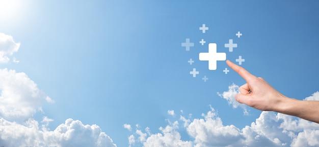 Mano masculina que sostiene el icono más sobre fondo azul. el signo más virtual significa ofrecer cosas positivas como beneficios, desarrollo personal, ganancias de redes sociales, seguro médico, conceptos de crecimiento.