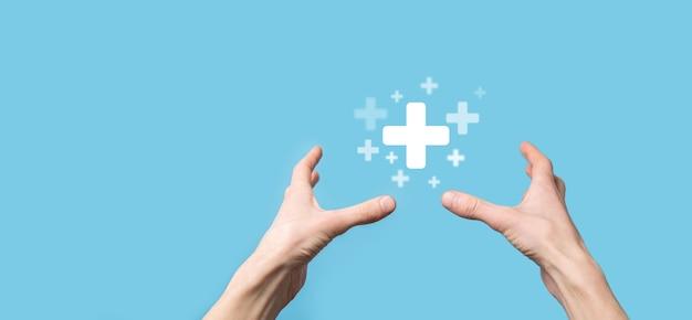 Mano masculina que sostiene el icono más sobre fondo azul. el signo más virtual significa ofrecer cosas positivas como beneficios, desarrollo personal, ganancias de redes sociales, seguros de salud, conceptos de crecimiento.