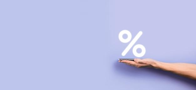Mano masculina que sostiene el icono de porcentaje de tasa de interés sobre fondo azul. concepto de tasas de interés financieras e hipotecarias.banner con espacio de copia