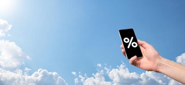 Mano masculina que sostiene el icono de porcentaje de tasa de interés sobre fondo de cielo azul. concepto de tasas de interés financieras e hipotecarias. banner con espacio de copia.