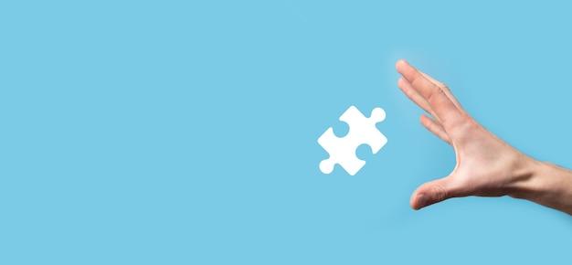 Mano masculina que sostiene el icono del rompecabezas en la superficie azul