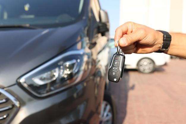 Mano masculina que sostiene las llaves cerca del primer del coche nuevo. concepto de alquiler de coches