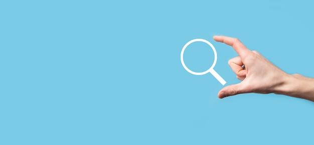 Mano masculina que sostiene la lupa, icono de búsqueda sobre fondo azul. concepto de optimización de motores de búsqueda, soporte al cliente. navegación de información de datos de internet. concepto de trabajo en red.