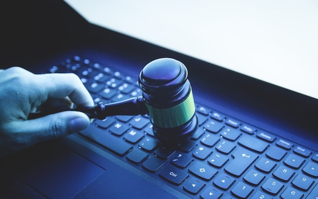 Mano masculina que sostiene el martillo del juez en el teclado del ordenador portátil. crimen de internet