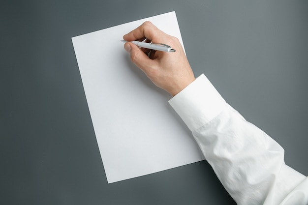 Mano masculina que sostiene la pluma y la escritura en una hoja vacía en la pared gris para texto o diseño. plantillas en blanco para contacto, publicidad o uso en negocios. finanzas, oficina, compras. copyspace.