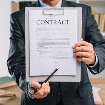 Mano masculina que sostiene la pluma que señala en el lugar de la firma en un documento de contrato