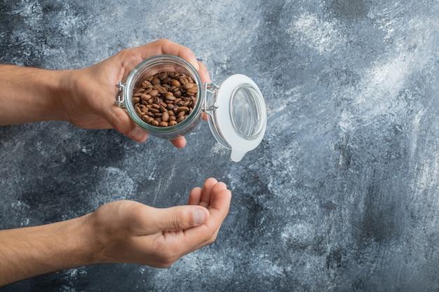 Mano masculina que sostiene el tarro de cristal de granos de café aromáticos sobre fondo de mármol