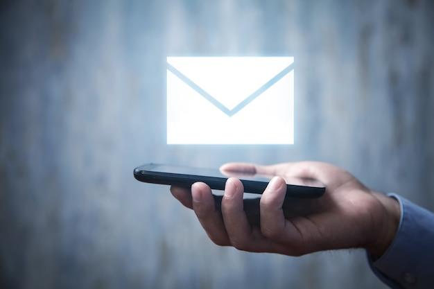 Mano masculina que sostiene el teléfono inteligente con el icono de correo electrónico.