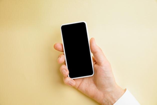 Mano masculina que sostiene el teléfono inteligente con pantalla vacía en la pared amarilla para texto o diseño. plantillas de gadgets en blanco para contacto o uso en negocios. finanzas, oficina, compras. copyspace.