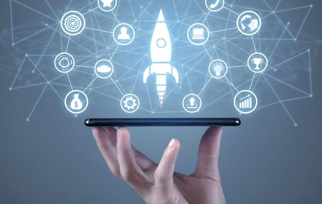 Mano masculina que sostiene el teléfono inteligente. símbolo de cohete, iconos de negocios y red. negocio. puesta en marcha