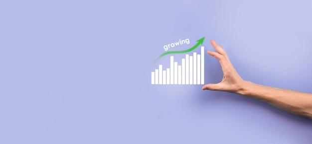 Mano masculina que sostiene el teléfono móvil inteligente con el icono del gráfico. comprobación del análisis del gráfico del crecimiento de los datos de ventas y del mercado de valores en las redes globales. estrategia empresarial, planificación y marketing digital