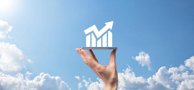 Mano masculina que sostiene el teléfono móvil inteligente con el icono del gráfico. comprobación del análisis del gráfico de crecimiento de los datos de ventas y del mercado de valores en las redes globales. estrategia empresarial, planificación y marketing digital.