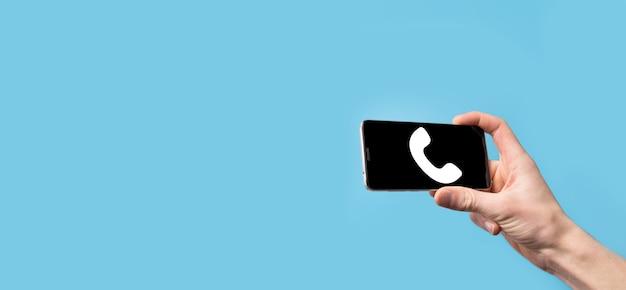 Mano masculina que sostiene el teléfono móvil inteligente con el icono de teléfono. llame ahora concepto de tecnología de servicio al cliente del centro de soporte de comunicación empresarial