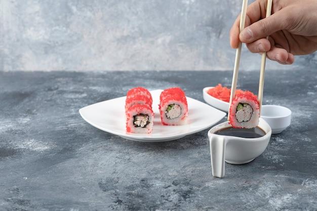 Mano masculina recogiendo sushi roll con palillos sobre fondo de mármol