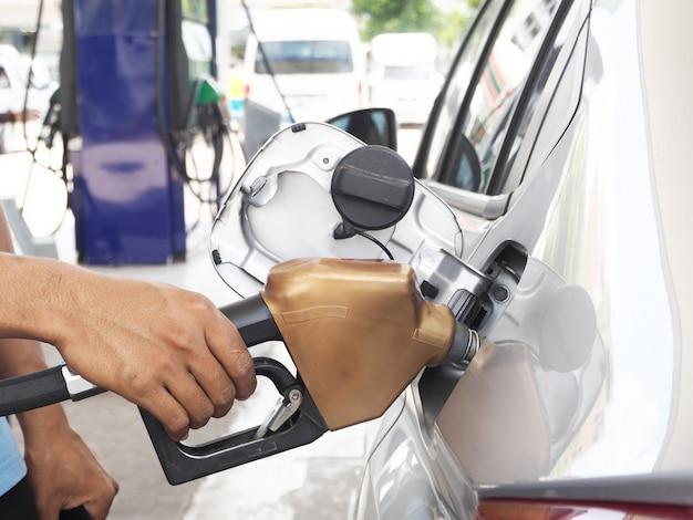 Mano masculina rellenando combustible al auto en una estación de llenado de gas