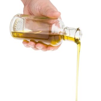Mano masculina sosteniendo una botella. aceite saliendo de una botella.