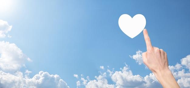 Mano masculina sosteniendo el corazón, como icono sobre fondo azul. concepto de bondad, caridad, amor puro y compasión.banner con espacio de copia.