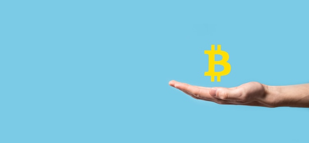 Mano masculina sosteniendo un icono de bitcoin sobre fondo azul. bitcoin cryptocurrency digital bit coin btc moneda tecnología negocios internet concepto.