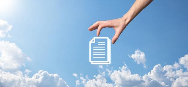 Mano masculina sosteniendo un icono de documento sobre fondo azul. concepto de tecnología de internet empresarial del sistema de datos de gestión de documentos. sistema de gestión de datos corporativos dms.