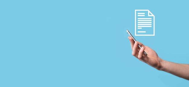 Mano masculina sosteniendo un icono de documento sobre fondo azul. sistema de datos de gestión de documentos concepto de tecnología de internet empresarial. sistema de gestión de datos corporativos dms.