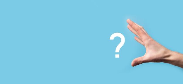 Mano masculina sosteniendo el icono de signo de interrogación sobre fondo azul.banner con espacio de copia. lugar para el texto.