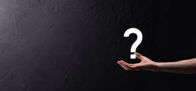 Mano masculina sosteniendo el icono de signo de interrogación sobre fondo oscuro.banner con espacio de copia. lugar para el texto.