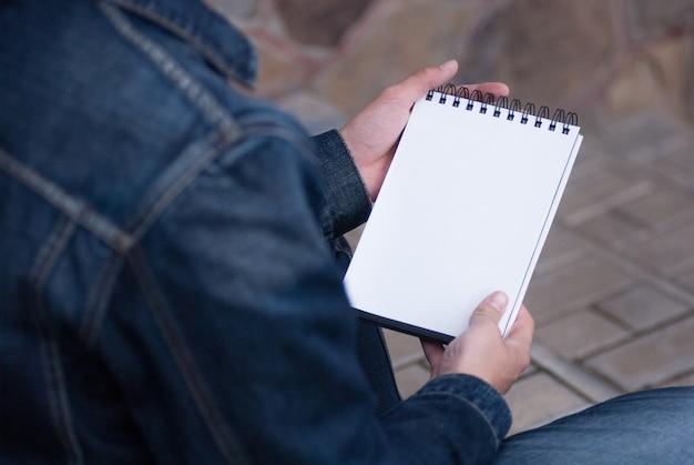Mano masculina sosteniendo un libro y sentado afuera