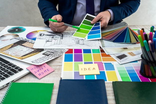 Mano masculina sosteniendo muestras de color con perspectiva interior. mano del diseñador de interiores trabajando con bocetos de apartamentos, muestras de materiales y colores