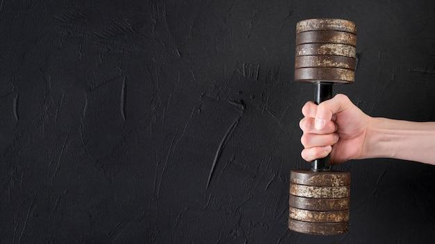 Mano masculina sosteniendo una pesa metálica