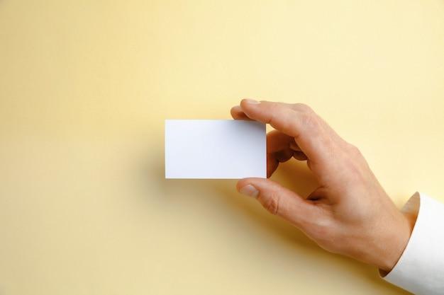 Mano masculina sosteniendo una tarjeta de visita en blanco sobre amarillo suave