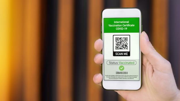 Mano masculina sosteniendo un teléfono inteligente con certificado de vacunación internacional código qr covid-19