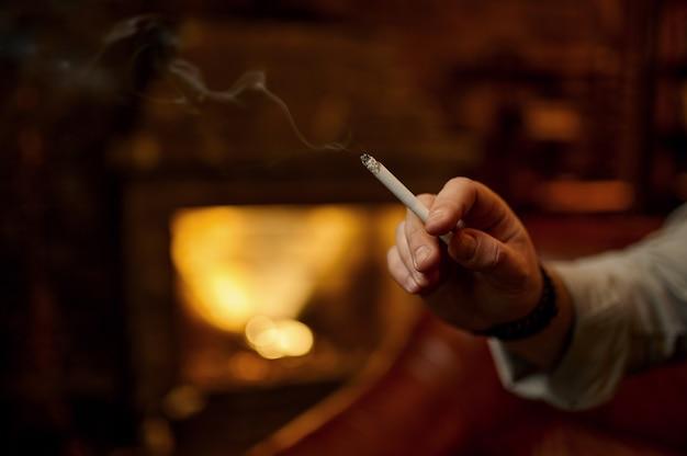 Mano masculina sostiene un cigarrillo, rico interior de oficina con chimenea. cultura del tabaquismo, sabor específico. ocios del fumador en casa