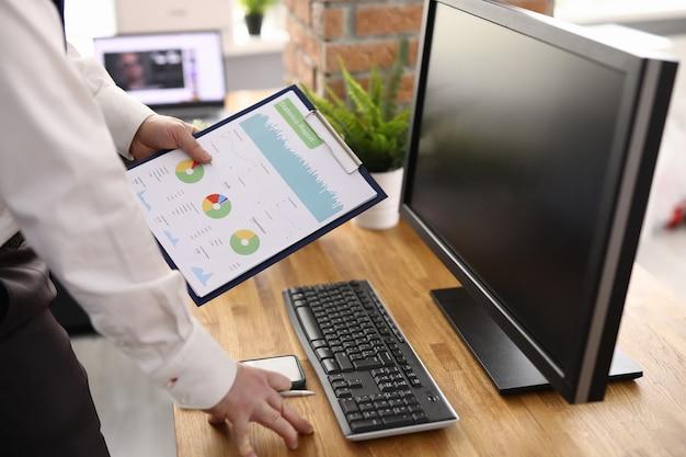 La mano masculina sostiene gráficos con indicadores comerciales en el lugar de trabajo. concepto de desarrollo de pequeñas y medianas empresas.