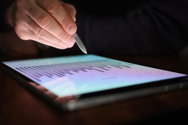 La mano masculina sostiene el lápiz sobre la pantalla de la tableta con gráficos comerciales en la oscuridad