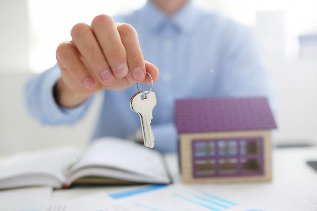 La mano masculina sostiene la llave de la cerradura en la mano contra el telón de fondo