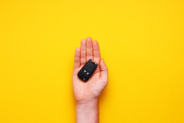 La mano masculina sostiene las llaves del coche sobre fondo amarillo. concept car, alquiler de autos, obsequio, lecciones de manejo, carnet de conducir. endecha plana, vista superior