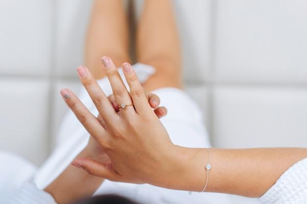 La mano masculina sostiene la palma femenina sobre fondo claro.
