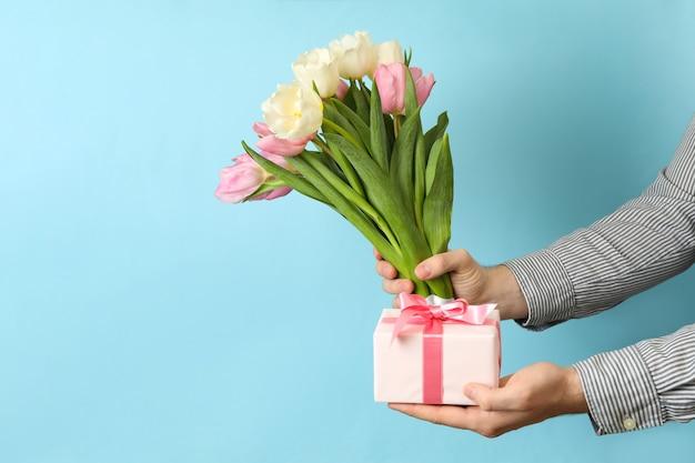 Mano masculina sostiene ramo de tulipanes y caja de regalo sobre fondo azul.