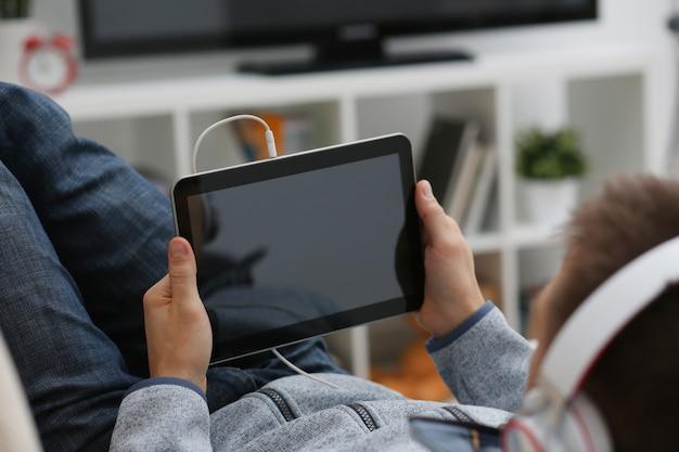 La mano masculina sostiene la tableta en el hogar mientras
