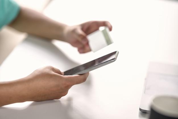 Mano masculina mediante teléfono móvil inteligente con tarjeta de crédito para pago o banca en línea.