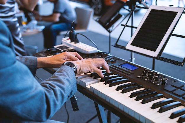 La mano masculina toca el piano en la fiesta abre una nueva sala de exposición.