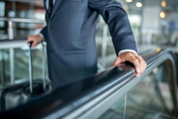 Mano masculina tocando el pasamanos en la escalera mecánica