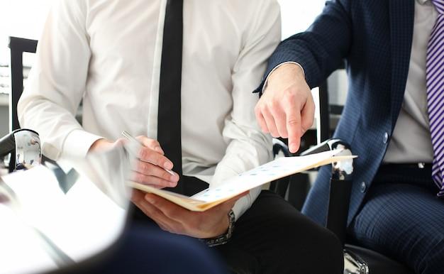 Mano masculina en traje y corbata mostrando algo importante en el documento de entrevista fiscal