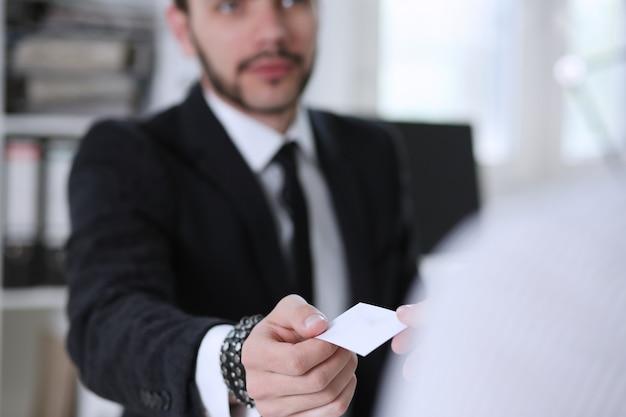 La mano masculina en traje da la tarjeta de visita en blanco al primer visitante femenino.