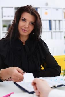 La mano masculina en traje da la tarjeta de visita en blanco al retrato femenino del visitante