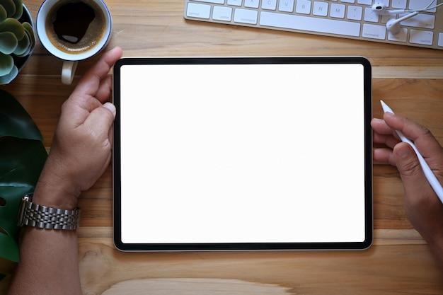 Mano masculina usando tableta blanca en espacio de trabajo