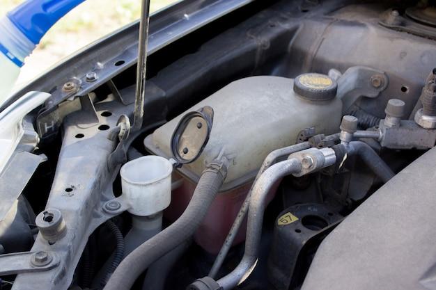Mano masculina vierte líquido en la lavadora debajo del capó de un automóvil