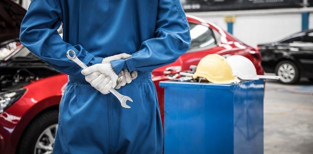 Mano del mecánico de automóviles haciendo servicio y mantenimiento de automóviles.